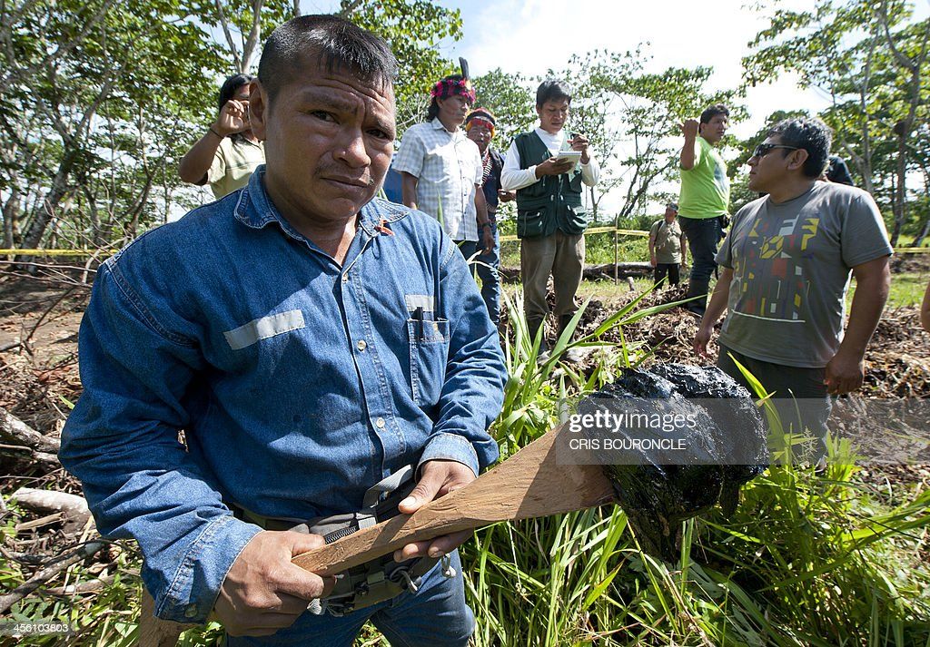 A resident of the town of Nuevo Andoas, some 4000 km northeast of Lima, shows a lump of tar to James Anaya (not in the picture), United Nations appointed Special Rapporteur on the Situation of Human Rights and Fundamental Freedom of Indigenous Peoples, as evidence of oil residues and other contaminants hidden by oil companies close to the Ullpayacu lagoon, during his December 11, 2013 visit to indigenous communities affected by the contamination caused by industrial and petroleum operations. AFP PHOTO/CRIS BOURONCLE