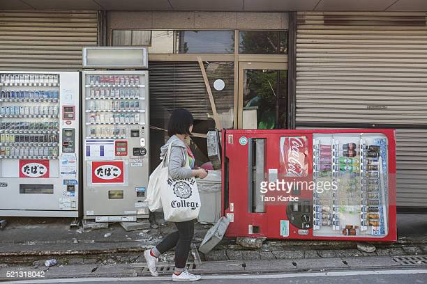 A resident passes by a broken vending machine after an earthquake on April 15 2016 in Kumamoto Japan At least nine people have died in a powerful...