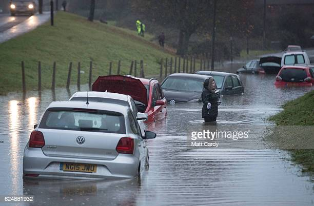 A resident passes cars that have been submerged under several feet of flood water in Hartcliffe after heavy rain fall from last night and today...