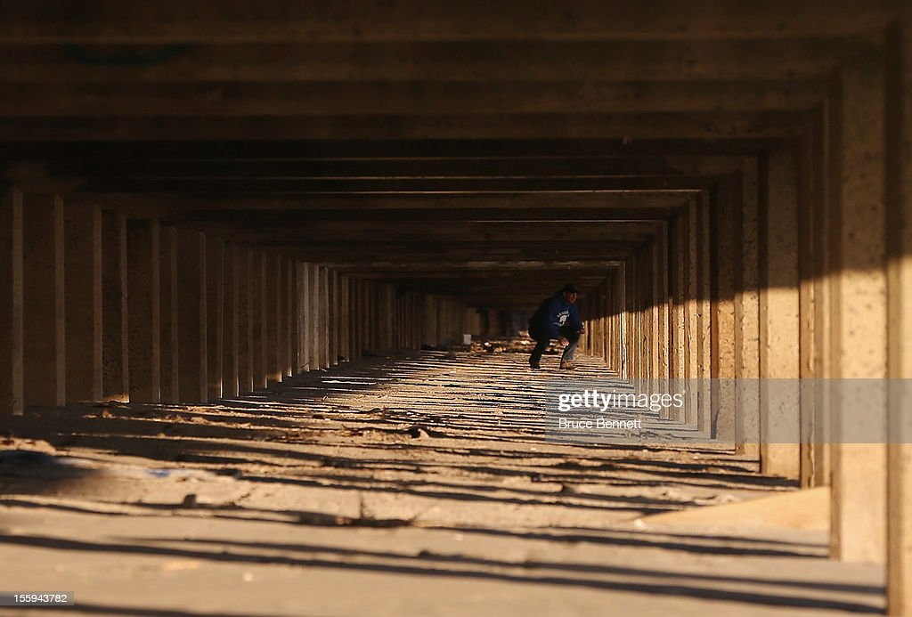 A resident peers out at the beach from under a destroyed section of the boardwalk as Long Islanders continue their clean up efforts in the aftermath of Superstorm Sandy on November 9, 2012 in Long Beach, New York. New York Gov. Andrew M. Cuomo has said that the economic loss and damage to homes and business caused by Sandy could total $33 billion in New York, according to published reports.