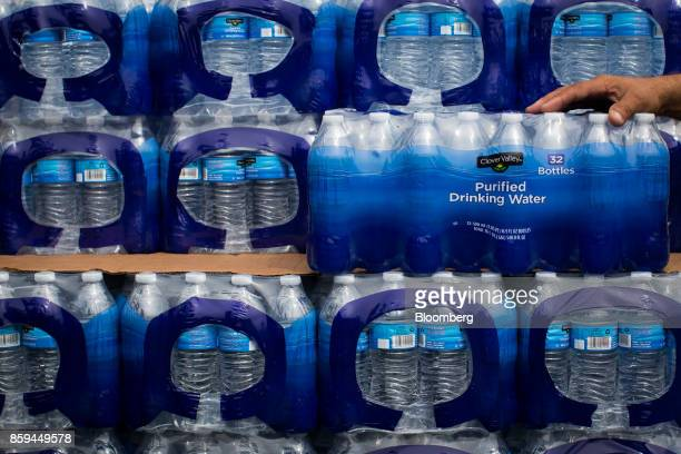 A resident places a hand on cases of bottled drinking water in Adjuntas Puerto Rico on Friday Oct 6 2017 US lawmakers pledged to back Puerto Rico's...