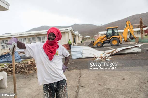 A resident poses before to clean the rubbles at Saint Martin III's College in the Orleans neighborhood eleven days after the passage of hurricane...