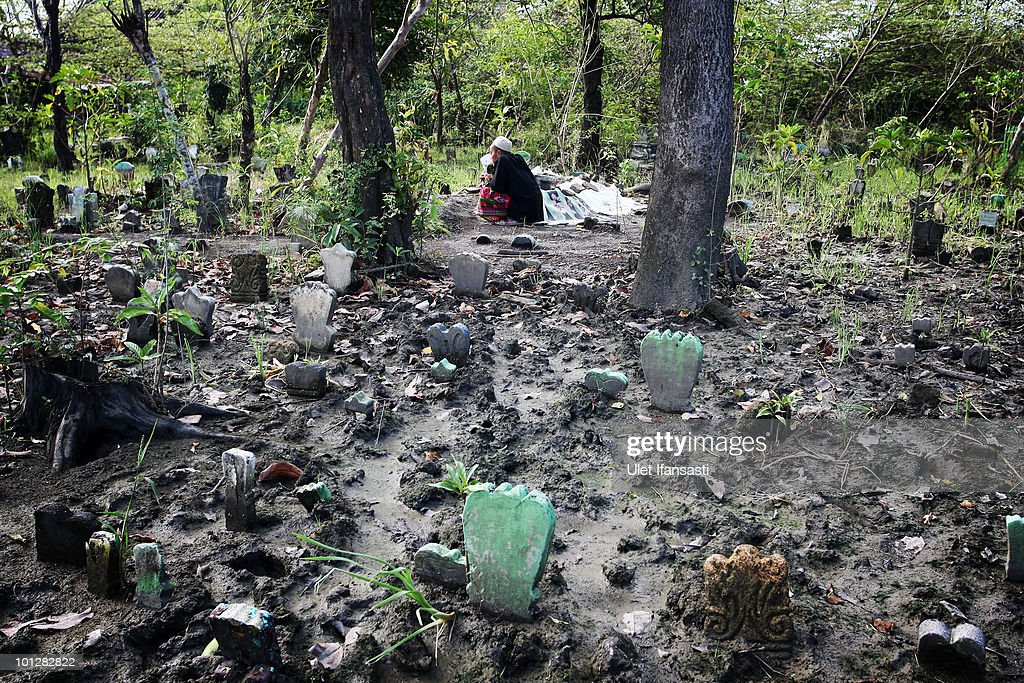 A resident prays at a public cemetery mostly submerged in mud from the volcano 'Lusi' on May 30, 2010 in the subdistrict of Porong in Sidoarjo, East Java, Indonesia. Mud and gases continue to spew from Lusi four years after it first erupted, suspected to be triggered by the drilling activities of Indonesian oil and gas exploration company Lapindo Brantas. The initial eruption engulfed entire communities, wiping out villages and killing 13 people. Mud flow from the volcano continues at a rate of up to 150,000m3 per day, and to date has displaced tens of thousands of people.