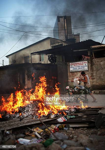 A resident prepares to burn trash at a garbage fire in the Vila Autodromo 'favela' community as Olympic Park construction stands at top on October 10...