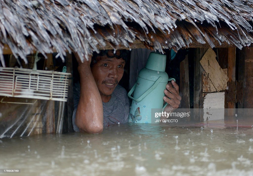 A resident prepares to leave his home through floodwaters in the farming town of Novaleta, some 26 kilometres outside Manila on August 19, 2013. Torrential rain paralysed large parts of the Philippine capital on August 19 as neck-deep water swept through homes, while floods in northern farming areas claimed at least one life. AFP PHOTO / Jay DIRECTO
