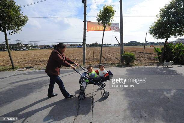 A resident pushes a pram with her babies at Qigang village in Pudong district a proposed site of the Disney park in Shanghai on November 4 2009 China...