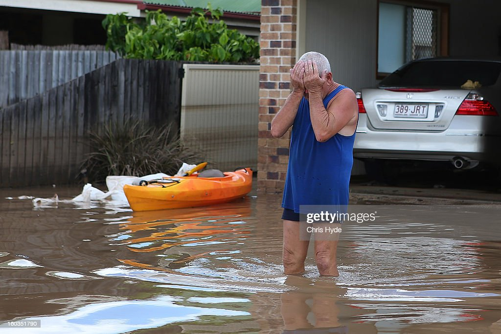 A resident reacts to the damage to his house as parts of southern Queensland experiences record flooding in the wake of Tropical Cyclone Oswald on January 30, 2013 in Bundaberg, Australia. Flood waters peaked at 9.53 metres in Bundaberg yesterday and began receding overnight, as residents and relief teams prepare to clean-up debris. Four deaths have been confirmed in the Queensland floods and the search is on for two men though to be missing in floodaters in Gatton.