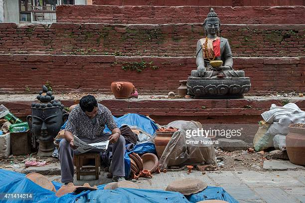 A resident reads a newspaper in one the temporary street shelters near Basantapur Durbar Square on April 28 2015 in Kathmandu Nepal A major 78...
