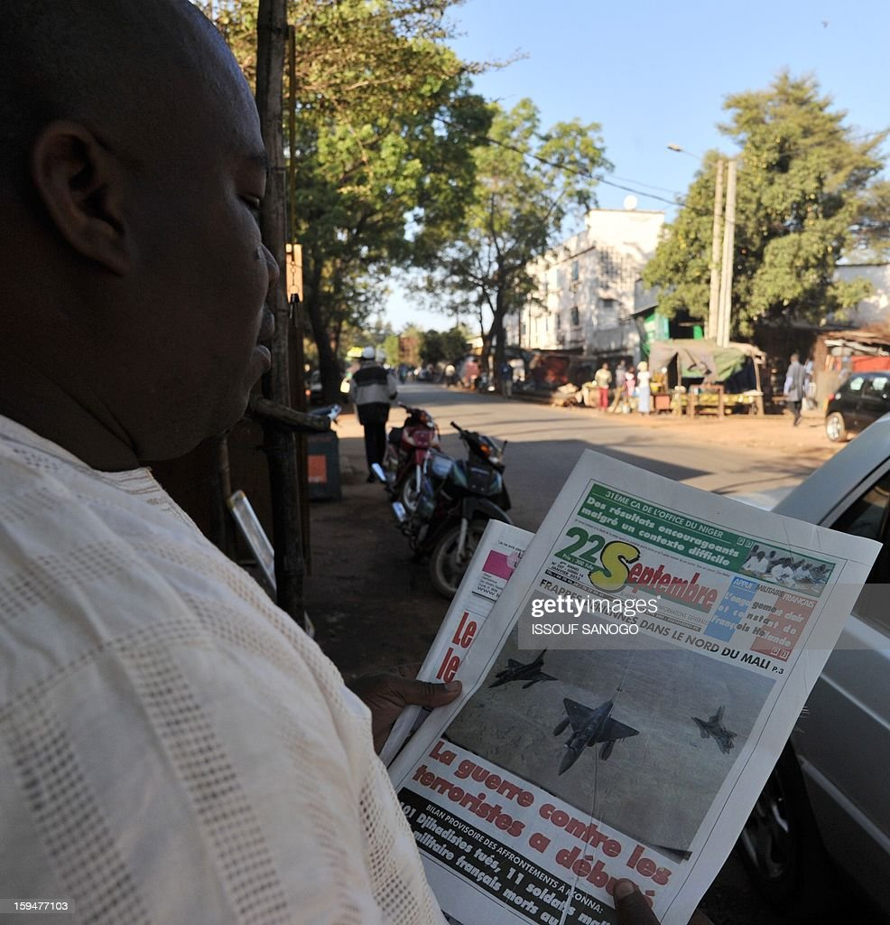 A resident reads a newspapers focusing on France's military intervention to turn back the terrorist threat in Mali on January 14, 2013 in Bamako.