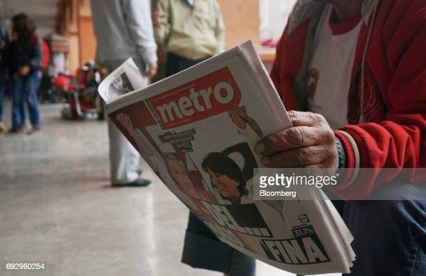 A resident reads the Metro newspaper featuring the cover images of Alfredo del Mazo Institutional Revolutionary Party candidate for governor of the...