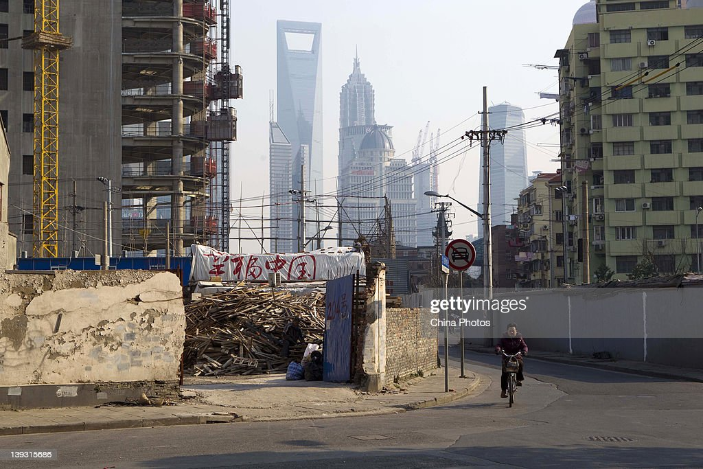 A resident rides a bike past a construction site in the background of skyscrapers in the Lujiazui Financial District at the North Bund on February 19, 2012 in Shanghai, China. According to local media, the North Bund area will be reconstructed as a international shipping and financial zone, a modern commercial and high-end residential area, and recreation center.