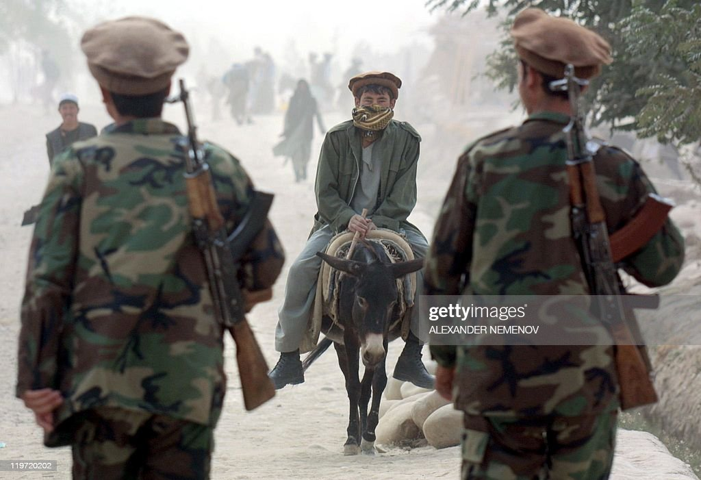 A resident riding a donkey is facing two Northern Alliance soldiers in the village of Khwaja Bahaulldin Northern Afghanistan some 15 kms from the...