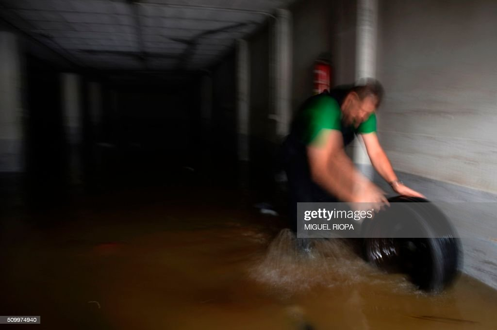 A resident rolls a car wheel out of a flooded garage after heavy rains in the village of Redondela, northwestern Spain, on February 13, 2016. / AFP / AFP or licensors / MIGUEL RIOPA