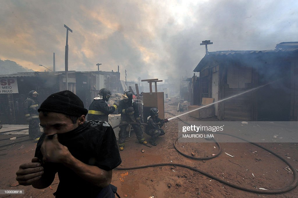 A resident runs out as firefighters extinguish a fire during an eviction at Capao Redondo shantytown, southern outskirts of Sao Paulo, Brazil, on August 24, 2009. Residents set huts on fire as a way to protest. Almost 800 families (some 1200 people) were removed from their huts in a huge area which was illegaly occupied by them since 2007. AFP PHOTO/Mauricio LIMA