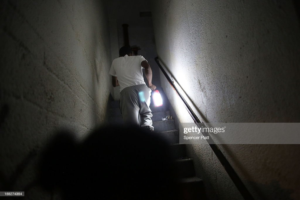 A resident runs up a darkened stairwell at the Red Hook Houses in Brooklyn where they currently have no water or electricity due to Superstorm Sandy on November 2, 2012 in the Brooklyn borough of New York City. Limited public transit has returned to New York and most major bridges have reopened but will require three occupants in the vehicle to pass. With the death toll currently over 90 and millions of homes and businesses without power, the US east coast is attempting to recover from the effects of floods, fires and power outages brought on by Sandy.