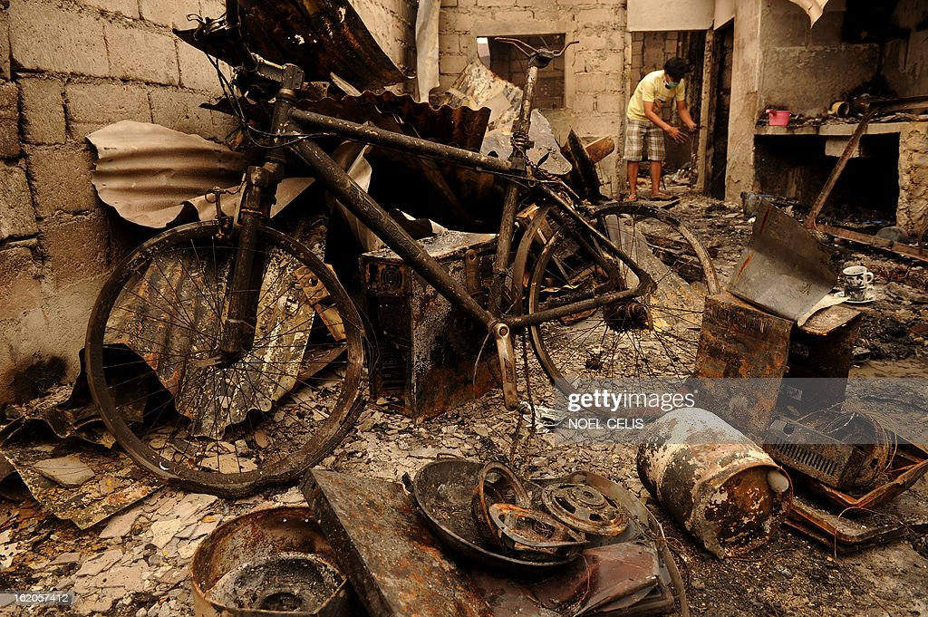 A resident searches for salvageable materials among debdris of destryoed houses after an overnight fire in a slum area in Manila on February 19, 2013. Almost 500 houses were destroyed, leaving 2,000 residents homeless according to a local media report.