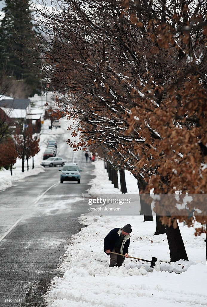 A resident shovels snow from his driveway on Conical Hill Road in Hanmer Springs on June 21, 2013 in Christchurch, New Zealand. Now, sleet, rain and heavy winds have hit the region causing power outages, some flooding and bringing trees down.