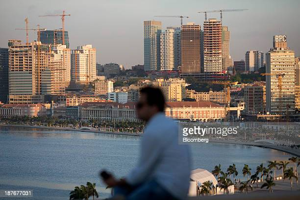 A resident sits and looks across the bay towards the city center skyline in Luanda Angola on Friday Nov 8 2013 Angola the largest crude oil producer...