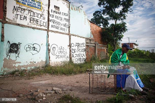 A resident sits draped in a Brazilian flag in the mostly demolished Vila Autodromo favela community on February 25 2016 in Rio de Janeiro Brazil The...