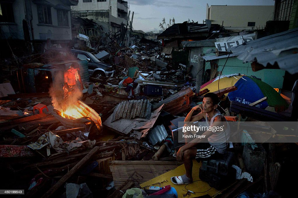 A resident sits in front of his destroyed house as another makes a fire in a devastated area in the aftermath of Typhoon Haiyan on November 17 2013...
