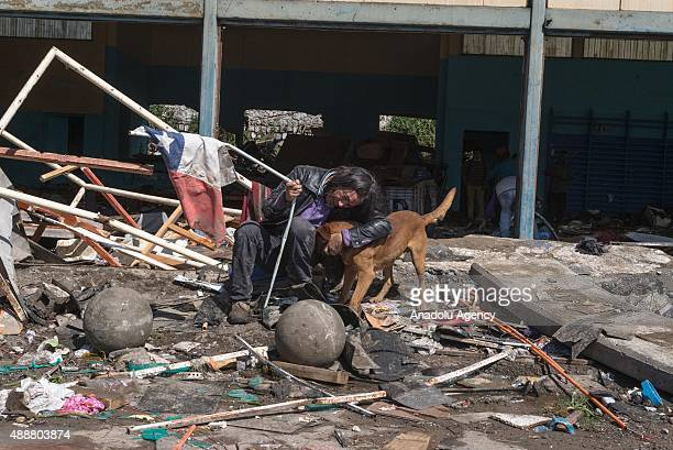 A resident sits with a dog among the debris of constructions in Coquimbo some 445 km north of Santiago on September 17 2015 in Chile On the evening...