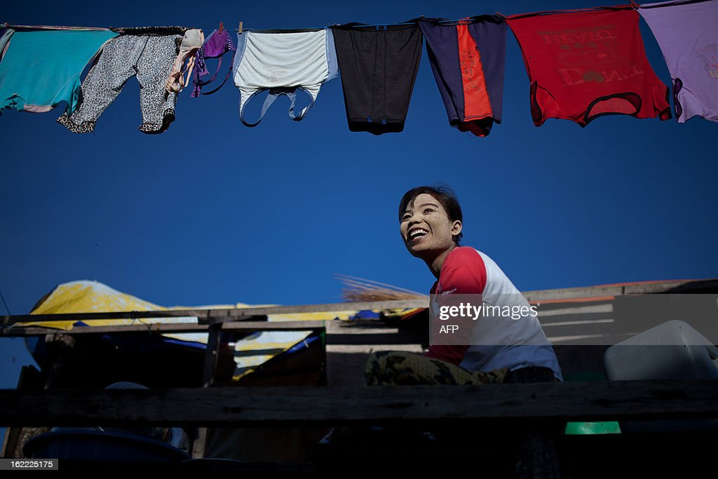 A resident smiles as she cleans her dishes in Tanjung Labian, near the location where suspected Philippine militants are holding off on February 21, 2013. Followers of a Philippine sultan who crossed to the Malaysian state of Sabah this month will not leave and are reclaiming the area as their ancestral territory, the sultan said on February 17 amid a tense stand off. AFP PHOTO / MOHD RASFAN