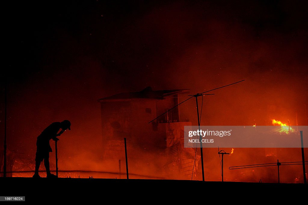 A resident smokes a cigarette on a roof as he looks at a fire that engulfed a residential area in Manila on January 19, 2013. Almost 50 houses were destroyed leaving a hundred families homeless, according to local media reports.