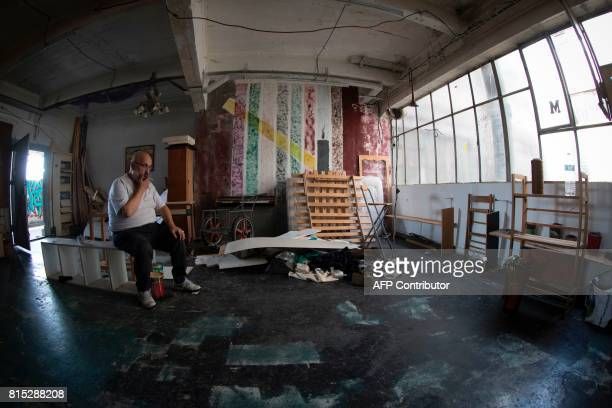 A resident smokes a cigarette on July 15 2017 in an apartment of the Cite de Jarry a former industrial building in Vincennes converted into an...