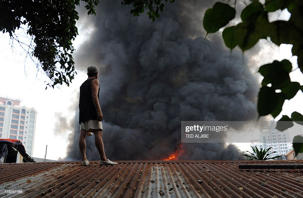 A resident standing on the roof of his house looks at a fire engulfing a shanty town at the financial district of Manila on July 11, 2013, leaving more than 1,000 people homeless according to city officials. There were no immediate reports of casualties from the blaze, which occurred mid-morning amid government plans to relocate thousands of families living in areas vulnerable to floods and typhoons.