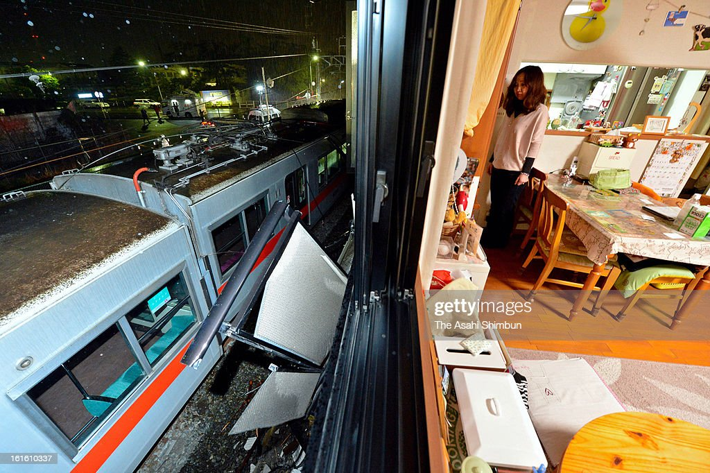 A resident stands by a window of her apartment where the balcony was destoryed by the derailed Sanyo Electric Railway Co. train after a collision with a truck near Arai Station on February 12, 2013 in Takasago, Hyogo, Japan. Fifteen people injured by the accident.