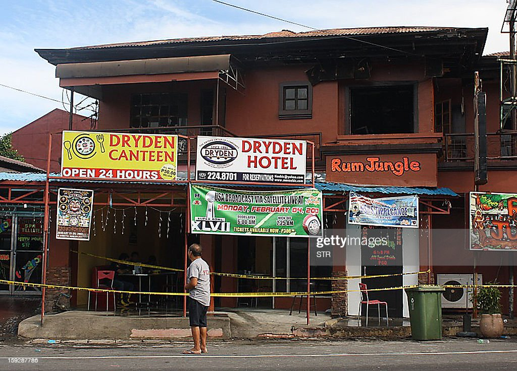 A resident stands in front of a small hotel after a fire broke out killing six people including three US and one South Korean citizen in the former US naval base, Olongapo City, north of Manila on January 11, 2013. Three US citizens and a South Korean man were among six people who died on January 11, when a fire razed a small hotel near a former US naval base in the Philippines, police said.
