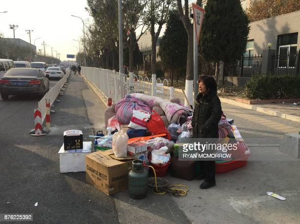 A resident stands next to her belongings along a road after being evacuated after a fatal housing block fire in Beijing on November 19 2017 Chinese...