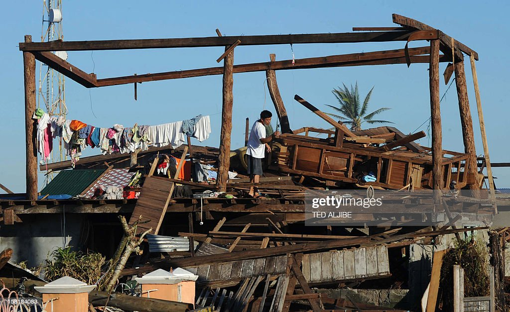 A resident stands on his destroyed house in Cateel town, Davao Oriental province on December 11, 2012, in the aftermath of Typhoon Bopha. The United Nations launched a 65 million USD global appeal on December 10 to help desperate survivors of a typhoon that killed more than 600 people and affected millions in the southern Philippines. AFP PHOTO / TED ALJIBE
