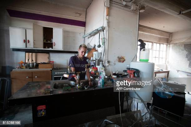 A resident stands on July 15 2017 in the kitchen of an apartment of the Cite de Jarry a former industrial building in Vincennes converted into an...