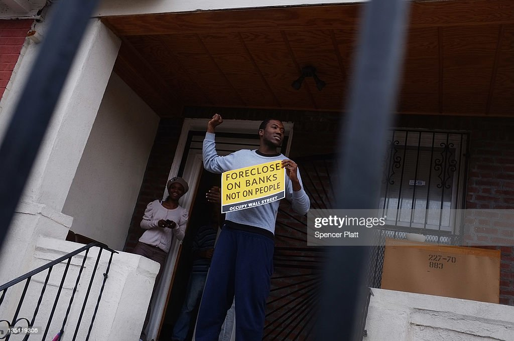 A resident stands outside of his home as community activists and over two hundred members of the Occupy Wall Street movement march in the impoverished community of East New York to draw attention to foreclosed homes in the community on December 6, 2011 in the Brooklyn borough of New York City. The group said they would occupy a home and would hand the property over to a homeless family. In what organizers are describing as a 'new frontier' for the movement, thousands of other Occupy Wall street protesters around the country participated in similar actions.