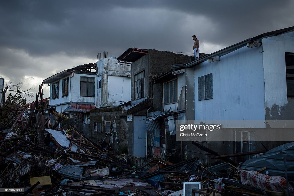 A resident surveys the surrounding damage from a rooftop on November 14 2013 in Leyte Philippines Typhoon Haiyan which ripped through Philippines...