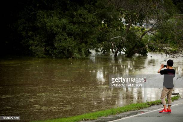 A resident takes photos as floodwaters caused by Cyclone Debbie recede in Beenleigh on April 2 2017 Rising floods continued to plague parts of...