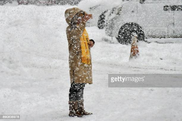 A resident takes pictures during snowfall in Yantai in China's eastern Shandong province on December 12 2017 A blue alert for a snowstorm and a...