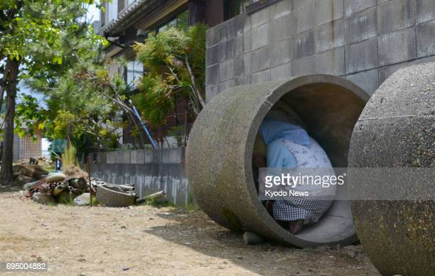 A resident takes shelter in a concrete culvert during an evacuation drill in Tsubame Niigata Prefecture on June 12 in the wake of North Korea's...