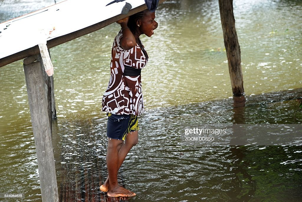 A resident takes shelter in a flooded area in Monrovia on July 1, 2016 following heavy rains. Heavy rains have cut the only road access to Liberia's main airport, leaving travellers to cross some sections by canoe, passengers told AFP on July 1. At certain points the sole road between the capital Monrovia and Roberts International Airport is 1.5 metres (five feet) underwater. DOSSO