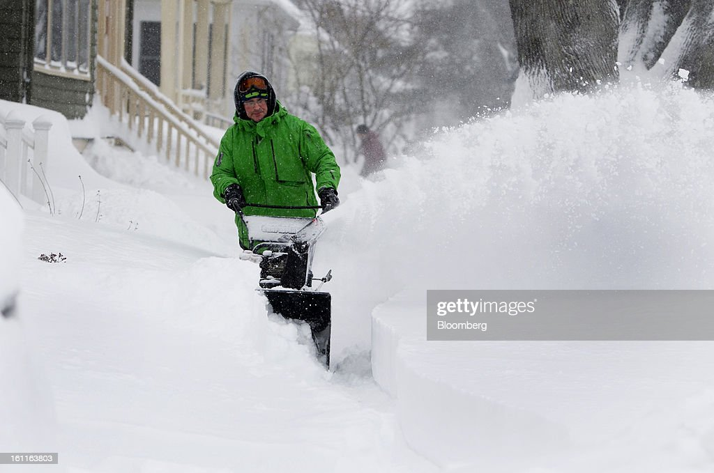 Resident Ted Miller clears snow from the sidewalk outside his home after Winter Storm Nemo in Somerville, Massachusetts, U.S., on Saturday, Feb. 9, 2013. More than two feet of snow fell on parts of the U.S. Northeast as high winds left hundreds of thousands of people in the region without power, closed highways and forced the cancellation of 4,700 flights. Photographer: Kelvin Ma/Bloomberg via Getty Images