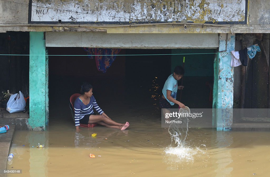 A resident throw flooded water with bucket as a woman sit on a chair after their house were inundated with flood water after a heavy monsoon rain in Dimapur, India north eastern state of Nagaland on Tuesday, June 28, 2016. Thousands of people were render homeless after heavy monsoon rain in the state.