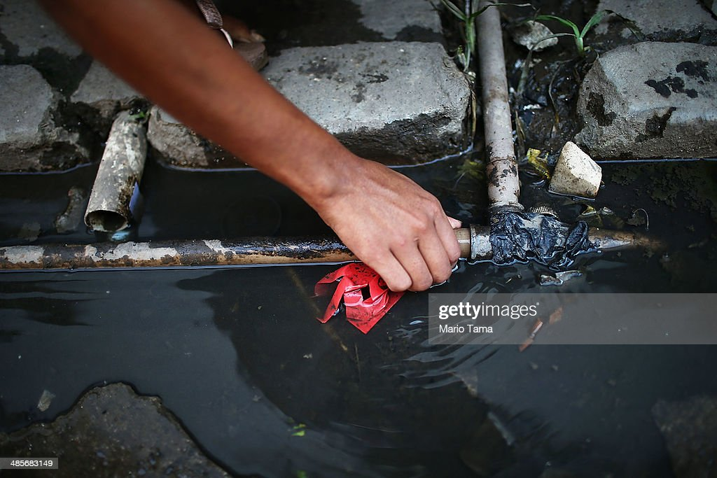 A resident tightens the seal on the one pipe with running water available to dozens of area residents in an impoverished section of the occupied Complexo da Mare, one of the largest 'favela' complexes in Rio, on April 19, 2014 in Rio de Janeiro, Brazil. The Brazilian government has deployed nearly 3,000 federal troops to occupy the group of violence-plagued slums ahead of the June 12 start of the 2014 FIFA World Cup. The group of 16 communities house around 130,000 residents and had been dominated by drug gangs and militias. Mare is located close to Rio's international airport and has been mentioned as a likely pacification target for the police amid the city's efforts to improve security ahead of the 2014 FIFA World Cup and Rio 2016 Olympic Games.