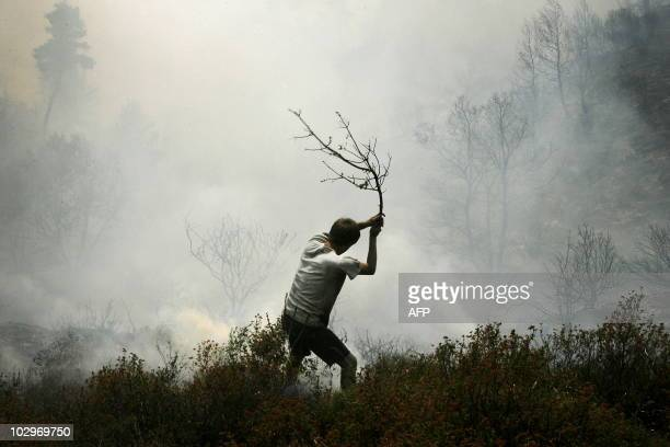 A resident tries to extinguish a fire in the Varnava village northeast of Athens on July 17 2010 Two large forest fires the first of the summer...