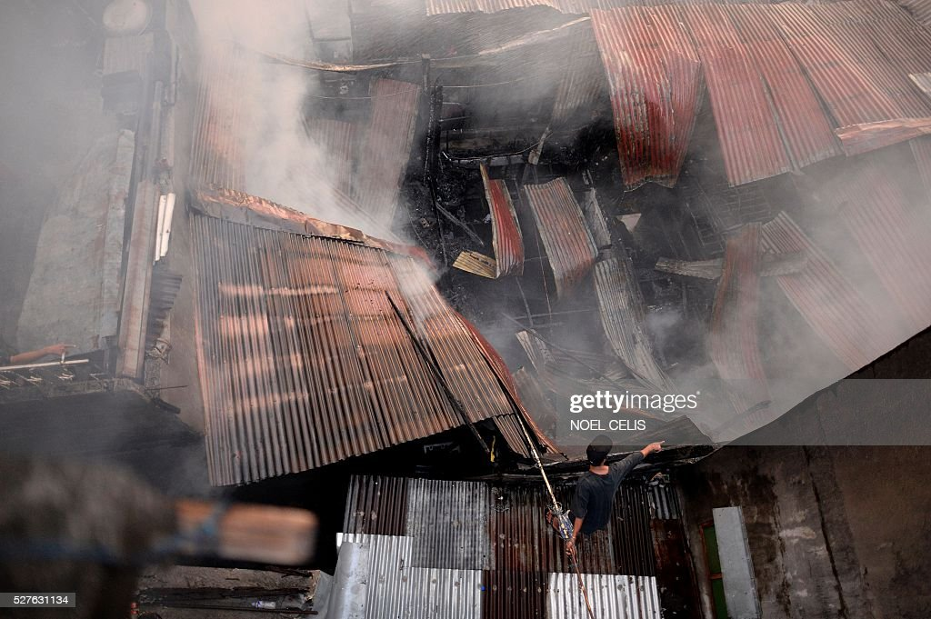A resident tries to put out a fire that swept over several houses in a residential area in Manila on May 3, 2016. No one was hurt in the fire, according to initial reports. / AFP / NOEL