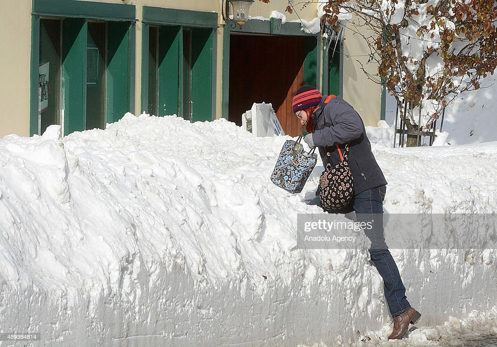 A resident tries to reach her workplace among roadside snow on November 21 2014 in Buffalo New York as the death toll attributed to Buffalo snow...