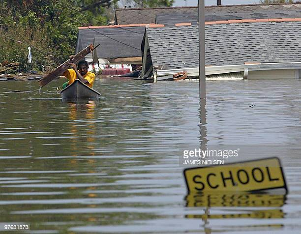 A resident uses a board to paddle through flood waters in New Orleans 30 August 2005 following Hurricane Katrina Hurricanebattered New Orleans was...