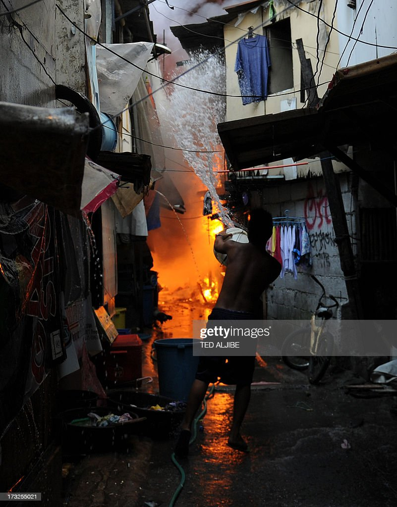 A resident uses a bucket to extinguish a fire burning houses in a shanty town in the financial district of Manila on July 11, 2013, leaving more than 1,000 people homeless according to city officials. There were no immediate reports of casualties from the blaze, which occurred mid-morning amid government plans to relocate thousands of families living in areas vulnerable to floods and typhoons.