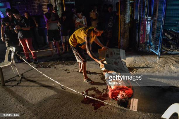 A resident uses a cardboard to cover the body of a shooting victim in Caloocan north of Manila Philippines March 30 2017 In the Philippines making...