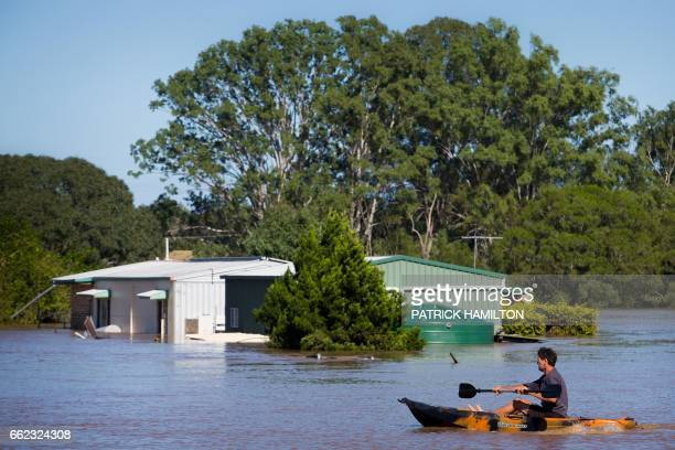 A resident uses a kayak to paddle past a house partially submerged under floodwaters caused by Cyclone Debbie to rescue a stranded cow on his...